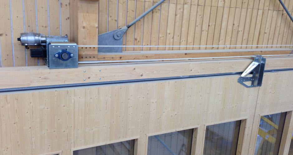 Grosse Holztore angetrieben mit einem Schiebetor GfA-ELEKTROMATE ST mittels Spezialvorgelege & Mitnehmer. Die Kraftübertragung wird mit einem Antriebsriemen gemacht